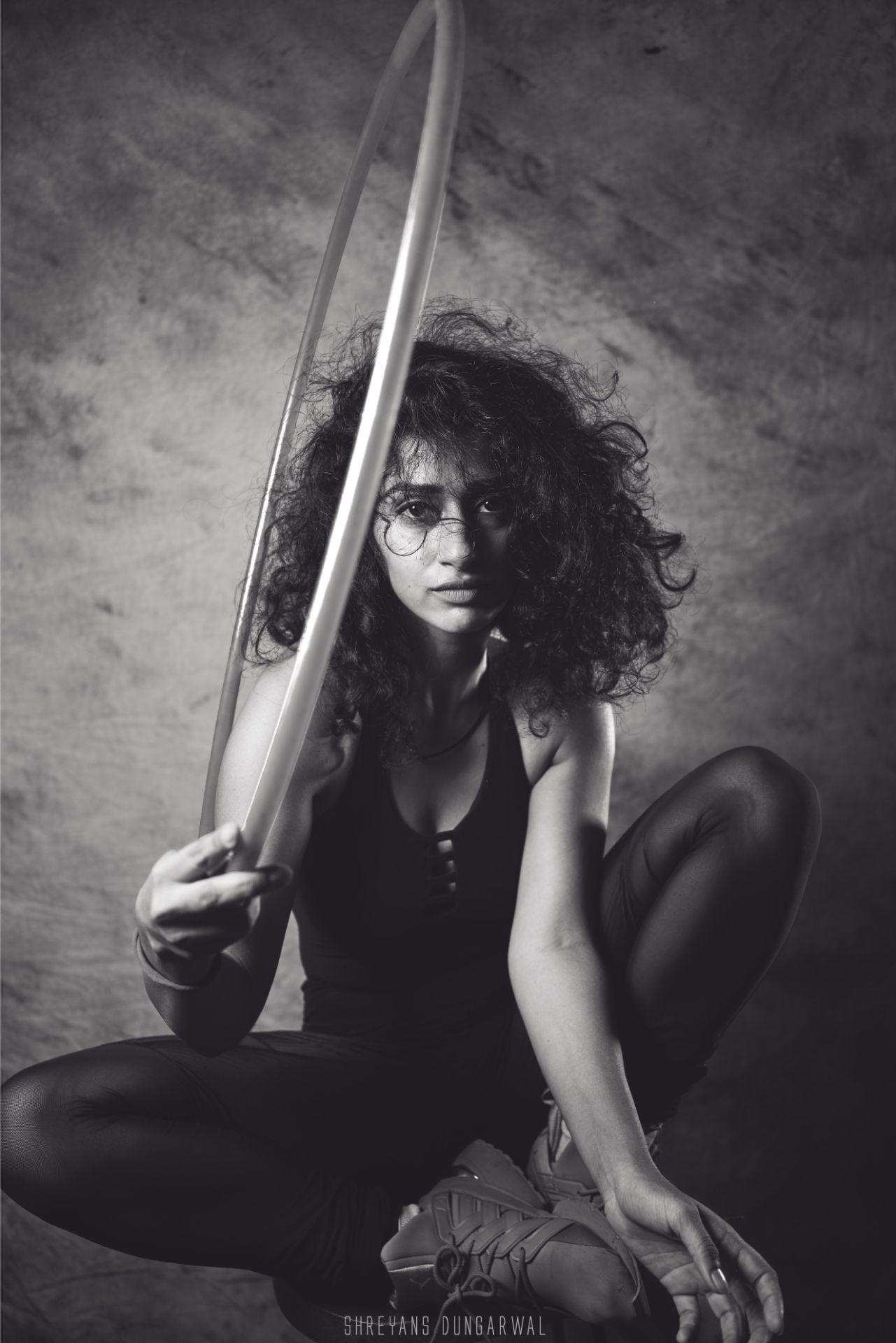 Posing with a hula hoop sitting on a chair staring into the lens. Black and white image.