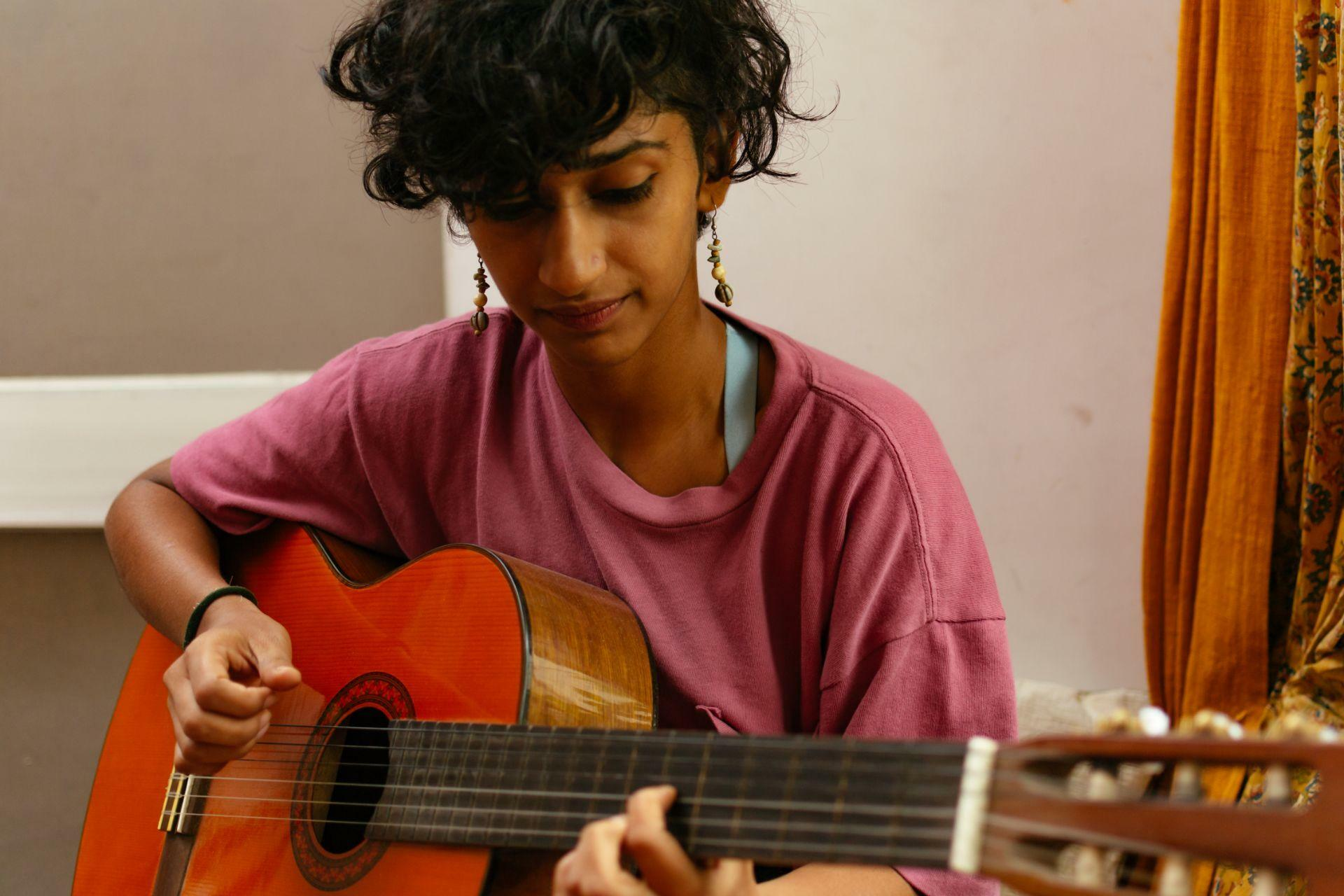 Girl playing guitar curly hair classical wearing pink